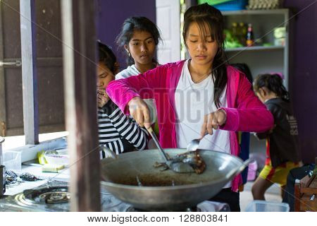 KOH CHANG, THAILAND - FEB 8, 2016: Unidentified children get food at lunch time at school by project Cambodian Kids Care to help deprived children in deprived areas on Koh Chang island.