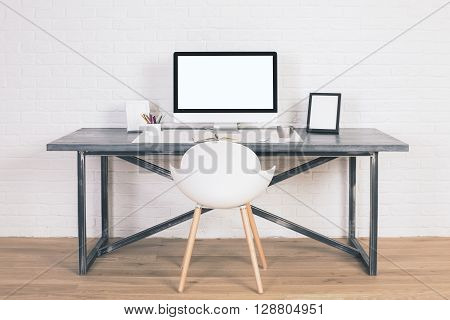 Front view of designer desk with blank white computer screen frames and other items with white chair next to it. Wooden floor and white brick wall background. Mock up poster