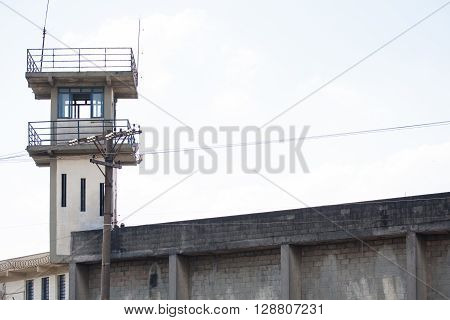 Prison security tower and power pole with blue sky and white clouds behind