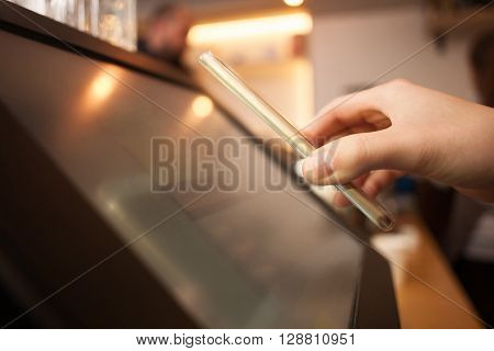 Close up of female hand holding a mobile phone near a screen. The woman is scanning on the payment machine by NFC