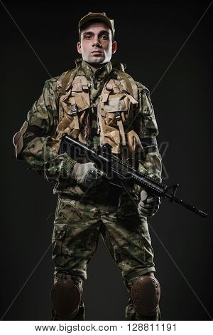 Military war conflict soldiers - Special forces soldier man hold Machine gun on a dark background. Military equipment NATO soldiers