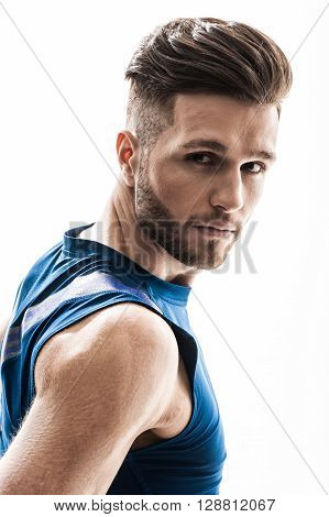 Portrait of attractive strong sportsman looking with confidence. He is standing in sportswear. Isolated