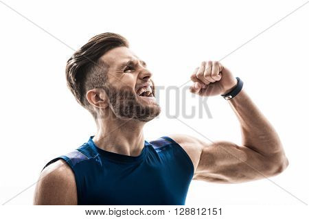 Waist up portrait of cheerful young sportsman celebrating his triumph. He is standing and shouting. The man is raising fist and laughing. Isolated on background