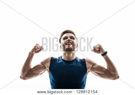 I am the winner. Portrait of attractive male athlete celebrating his victory. He is standing and raising his fists. The man is looking up and smiling