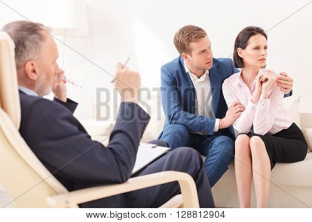 Young married couple is consulting the psychologist. The woman is looking aside with insult. Man is embracing her with love