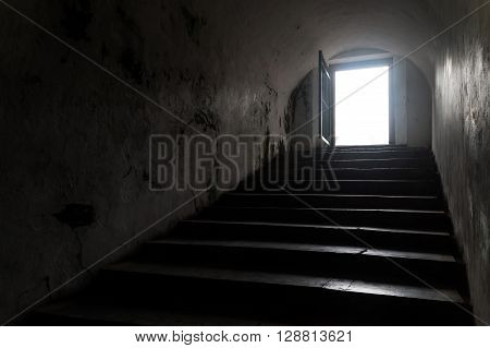 Silhouette inside of a dark tunnel facing to door outside