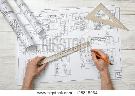 Close-up of architect hands holding centimeter ruler and pencil. Measuring process. Work place of draftsman, architect, constructor. Working process. Engineering work. Construction and architecture. Architect drawing. Measurement.