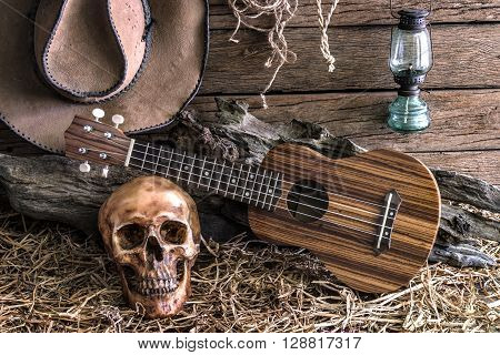 Still life human skull and ukulele on hay with traditional leather boots and american west rodeo brown felt cowboy hat background vintage and dark tone for horror halloween