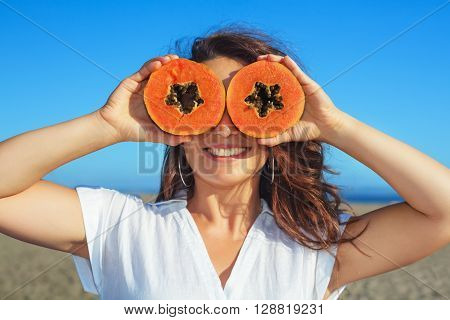 Funny photo of positive adult woman with smiling face holding in hands ripe fruit - orange papaya slices. Healthful food low calories breakfast on sea beach Healthy lifestyle on summer family holiday