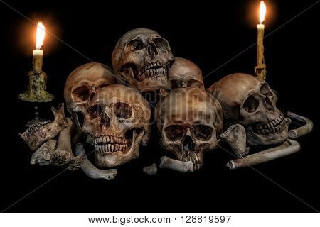 Pile of skulls and bones with two candles on black background. Genocides concept still life style.