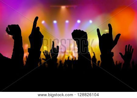 Concert crowd hands supporting rock and roll band performing live music on stage silhouettes of young people on rock gig enjoying.