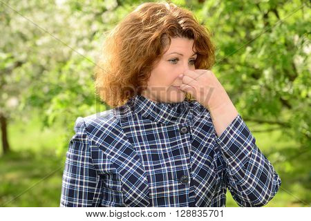 Woman suffering from allergic rhinitis in a lush park