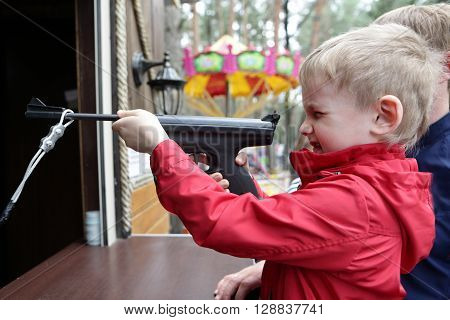 Boy shooting air pistol at the rifle range