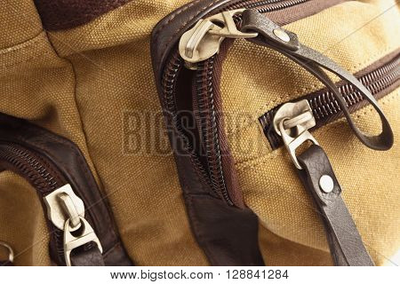 Zip closure on the brown bag on her pockets
