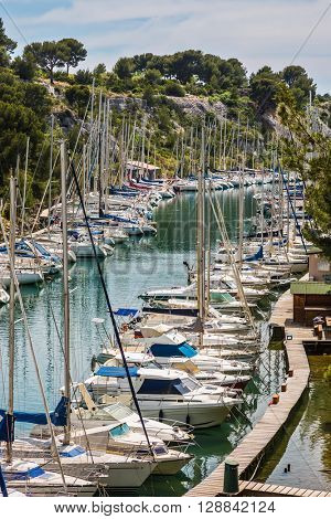 Calanque National Park - small fjords between Marseille and Cassis. White sailboats moored in rows near woody shore. Good weather in May
