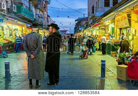 JERUSALEM ISRAEL - FEBRUARY 18 2016: Two friends-hasids dressed in traditional elegant clothes talking at the entrance of Mahane Yehuda market on February 18 in Jerusalem.