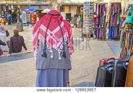 JERUSALEM ISRAEL - FEBRUARY 18 2016: The senior Palestinian in red kufiya walks in Omar Ben el-Hatab street along the souvenir shops on February 18 in Jerusalem.