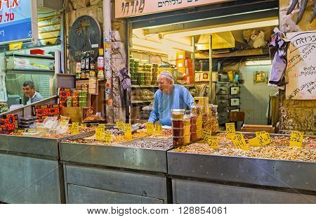 JERUSALEM ISRAEL - FEBRUARY 17 2016: The senior merchant in stall of Mahane Yehuda market offers the dried fruits sunflower seeds and various nuts on February 17 in Jerusalem.