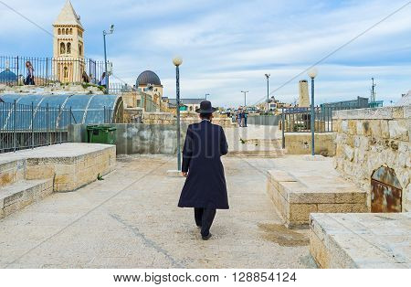 JERUSALEM ISRAEL - FEBRUARY 18 2016: The orthodox hasid walks along the roof in the old city on February 18 in Jerusalem.