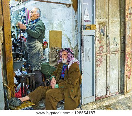 JERUSALEM ISRAEL - FEBRUARY 18 2016: The conversation of two old friends in shoemaker's workshop located in Muslim Quarter market on February 18 in Jerusalem.