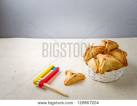Jewish holiday of Purim. Hamantaschen cookies and wooden gragger free space for text