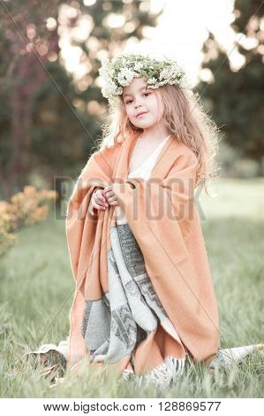 Cute kid girl 4-5 year old wearing flower wreath outdoors. Looking at camera. Childhood.