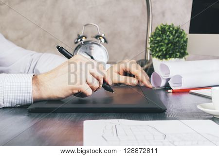 Sideview of male hands using graphic tablet on desktop with sketch and other items