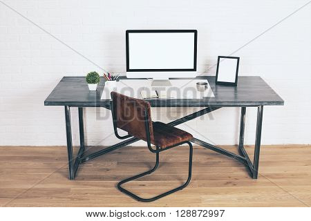 Front view of designer desk with blank white computer monitor frames and other items with brown chair next to it. Wooden floor and white brick wall background. Mock up