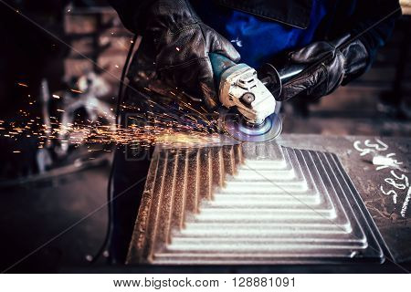 Electric wheel grinding on steel structure in industrial factory. worker cutting steel poster