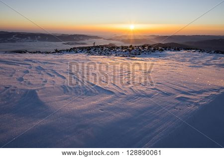 Winter sunrise over frozen landscape in Romanian Carpathians.