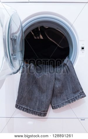 A close up of a washing machine loaded with clothes. Household appliance. poster