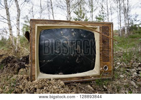 Old analog discarded television set in the forest.