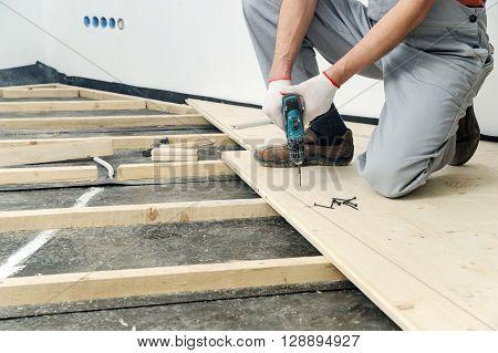 Installation of wooden floors. Worker twisting screw into the floor board.