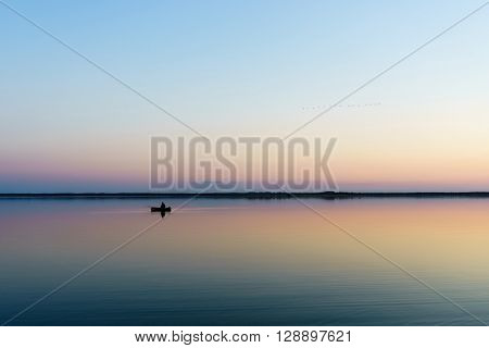 fishmonger in his traditional boat at sunrise.