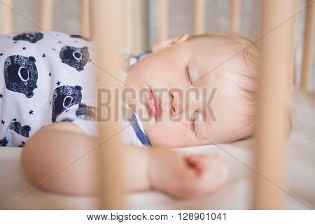 Peaceful adorable baby sleeping on his bed in a room. Soft focus. Sleeping baby concept. year-old babyboy sleeps at home close up