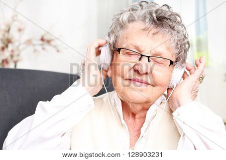 Elderly woman with headphones on listening to music