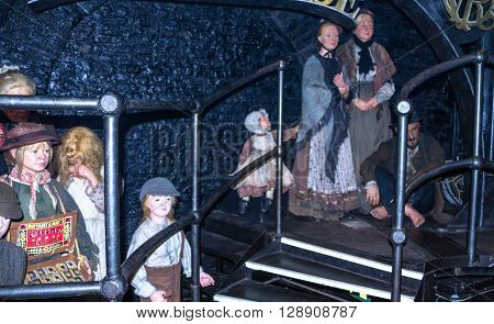 LONDON UK - JUNE 7 2015: Wax figures of young girls, women and children in costumes of the late 18th and early 19th century, the streets of the old town at Madame Tussauds museum. Madame Tussauds London is famous for recreating famous people and celebriti