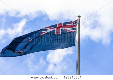 Australian flag waving against a blue sky with white clouds