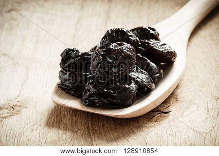 Healthy food good cuisine. Closeup dried plums prunes fruits on wooden spoon rustic table background