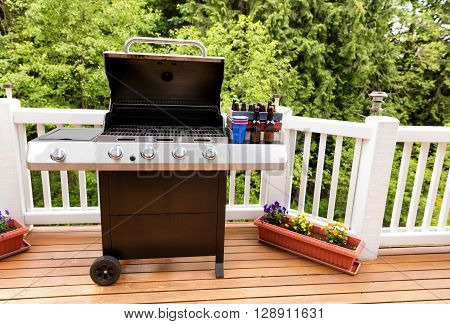 Open large barbecue cooker bottled beer cup and crate on cedar wood deck with trees in background.