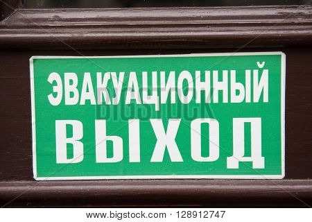 A signboard written in russian language hanging on a building gate. Exit sign.