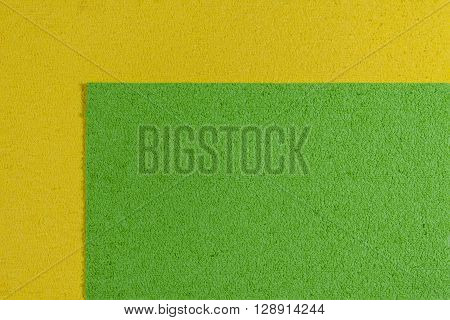 Eva foam ethylene vinyl acetate apple green surface on lemon yellow sponge plush background