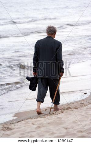 Old Man Walking On Beach