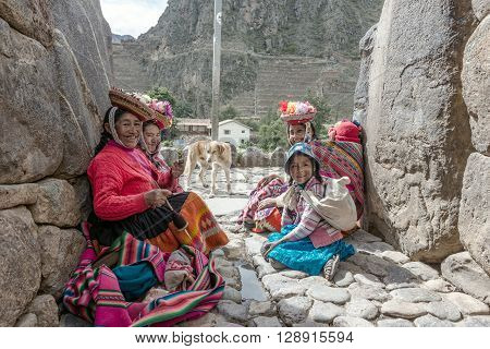 Ollantaytambo Peru - december 18 2014: Women and children in traditional Peruvian clothes break from posing with tourists in Ollantaytambo Peru