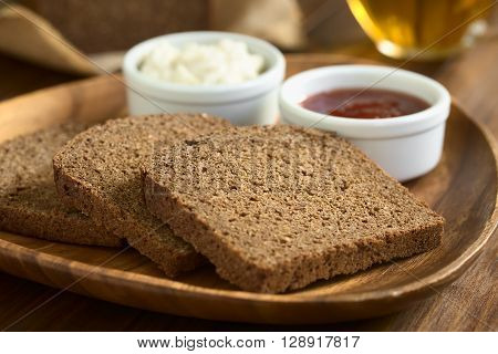 Slices of pumpernickel dark rye bread on wooden plate with jam and cream cheese cup of tea in the back photographed with natural light (Selective Focus Focus diagonally in the middle of the slice)