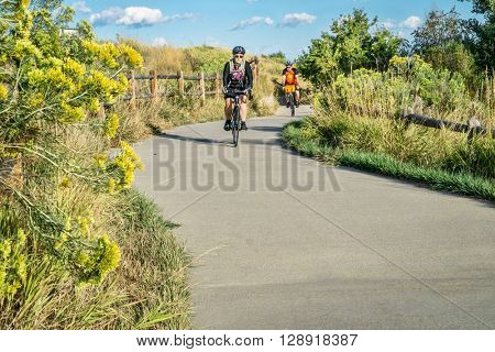 WINDSOR, CO, USA, SEPTEMBER 6, 2015: A couple is riding their bikes on the Poudre River Trail - paved path extending more than 20 miles between Timnath and Greeley, late summer morning.