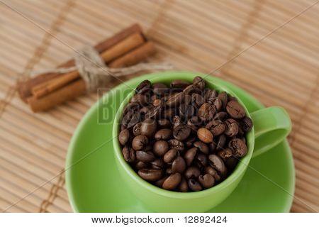 Kaffeebohnen in eine grüne Tasse