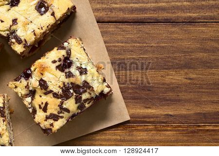 Cherry blondie or blond brownie cake baked with white and dark chocolate photographed overhead with natural light (Selective Focus Focus on the top of the cake pieces)