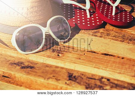 Sunglasses with straw hat and flip flop on wood table Summer vacation items Summer vacation background with essential of traveler
