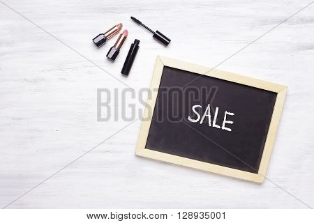 Chalkboard With Sale Written On It, And Cosmetic Products On Whi